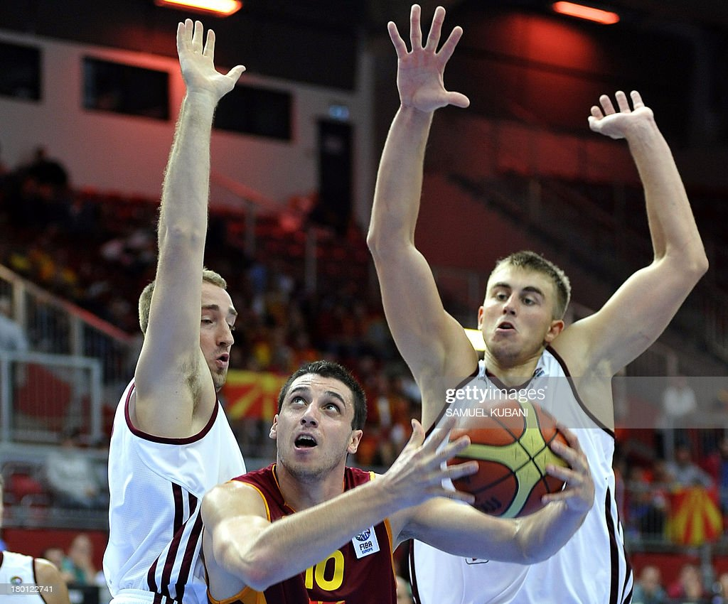 Macedonia's Vladimir Brckov (C) challenges Latvia's Martins Meiers (R) and Rihards Kuksiks (L) during the 2013 EuroBasket Championship group B match between F.Y.R. Macedonia and Latvia in Jesenice on September 9, 2013.