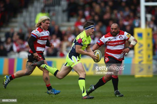MacGinty of Sale Sharks breaks away from Richard Hibbard and John Afoa of Gloucester Rugby during the Aviva Premiership match between Gloucester...