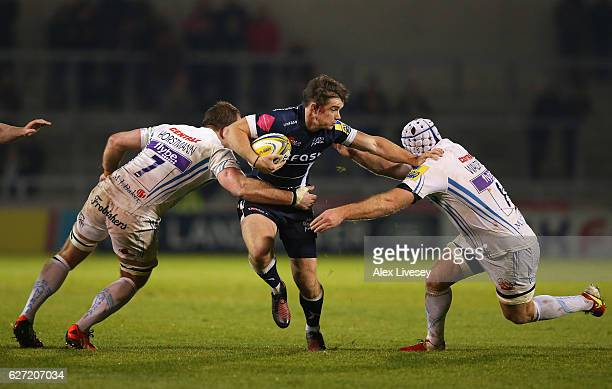 MacGinty of Sale Sharks is tackled by Thomas Waldrom and Kai Horstmann of Exeter Chiefs during the Aviva Premiership match between Sale Sharks and...