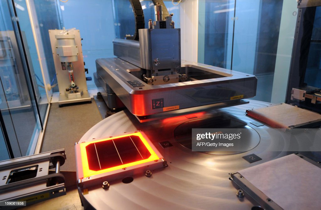 A machine assembles a photovoltaic cell on an assembly line at MPO Energy plant in Averton, western France, on January 7, 2013.