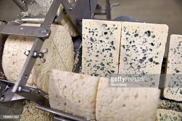 A machine cuts sections of Roquefort Societe 150years cheese for packaging at the LebrouRoquefort plant part of Groupe Lactalis in Roquefort France...