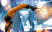 Machine learning and artificial intelligence technology concept. Blue tone of binary coded number and robot hand , laptop and automate wireless spot welding machine robot arm in smart factory.