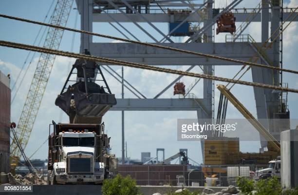 A machine loads ground granulated blast furnace slag on a truck from the Starry Sky bulk carrier ship at Port Canaveral in Cape Canaveral Florida US...
