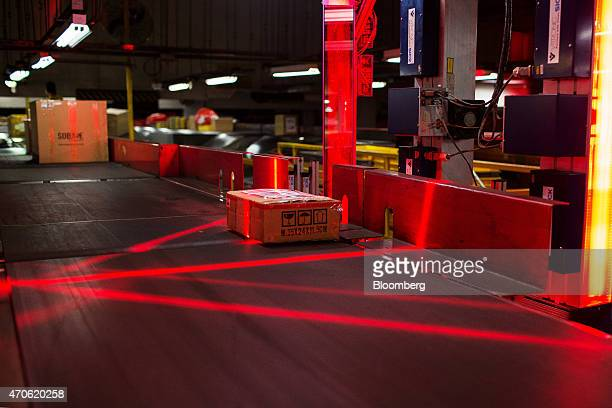 A machine scans a package as it moves along a conveyor during the overnight sort at the Central Asia Hub of DHL Worldwide Express a unit of Deutsche...