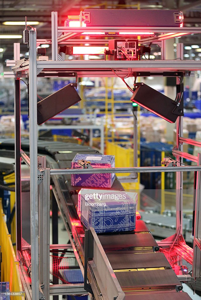 A machine scans mail parcels as they move along a conveyor belt in the main hall at the Russian Post automated sorting center in Podolsk, Russia, on Wednesday, Nov. 14, 2012. Alexander Kiselev, Russian Post's chief executive officer, needs to invest 200 billion rubles through 2020 to turn around a company that described its infrastructure as 'the most expansive, but the least efficient' in a strategy plan this year. Photographer: Andrey Rudakov/Bloomberg via Getty Images