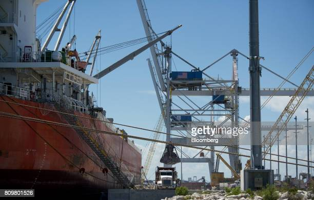 A machine unloads ground granulated blast furnace slag from the Starry Sky bulk carrier ship at Port Canaveral in Cape Canaveral Florida US on...