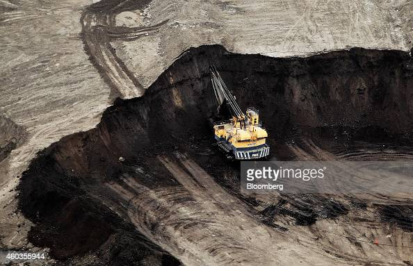 A machine works at the Suncor Energy Inc mine in this aerial photograph taken above the Athabasca Oil Sands near Fort McMurray Alberta Canada on...