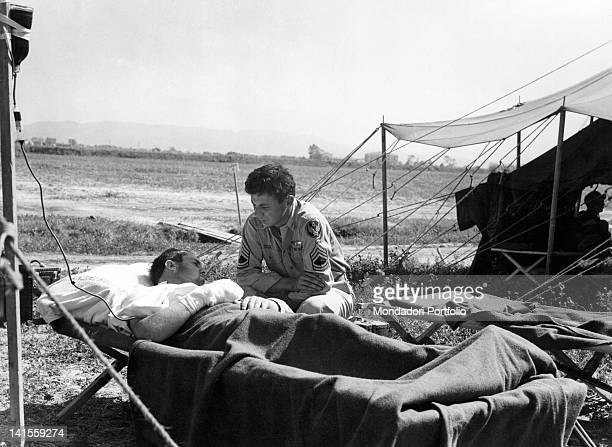 Machinegunner Sergeant Adolph J Paoli attending an injured soldier lying on a stretcher in an air base of the 15th division Italy August 1944