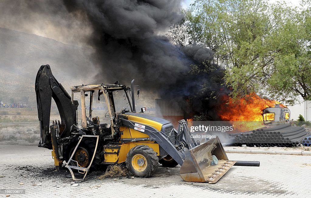 Machinery on fire at the De Doorns protest on the N1 highway on January 9, 2013, in Cape Town, South Africa. The protesting farm workers shut down the N1 by lighting tires on fire and placing large rocks on the road.