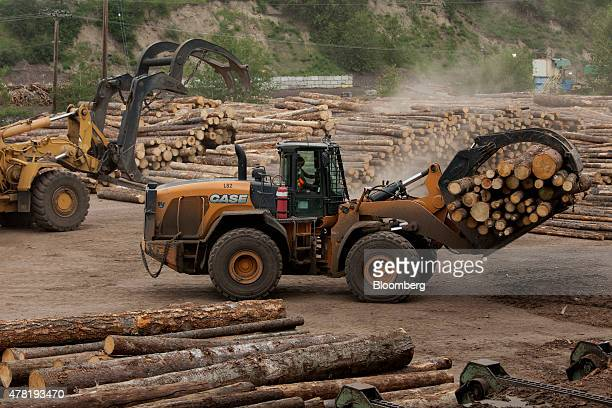 Machines move logs before being processed at the West Fraser Timber Co sawmill in Quesnel British Columbia Canada on Friday June 5 2015 Since the...