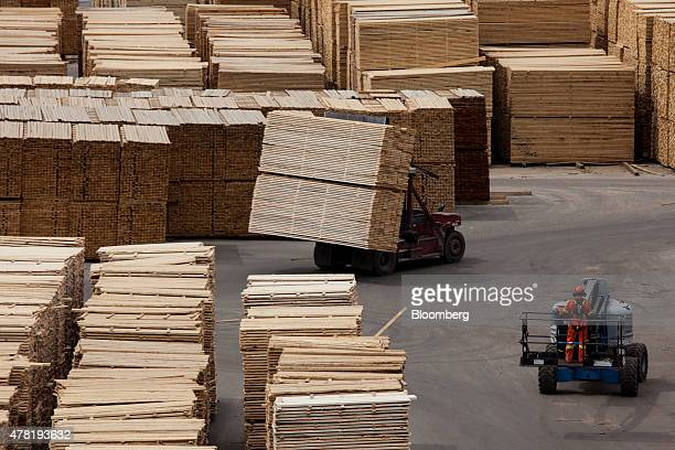 Machines move lumber ready for shipping at the West Fraser Timber Co sawmill in Quesnel British Columbia Canada on Friday June 5 2015 Since the late...
