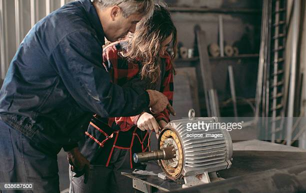 Machinist examining electric motor with voltmeter