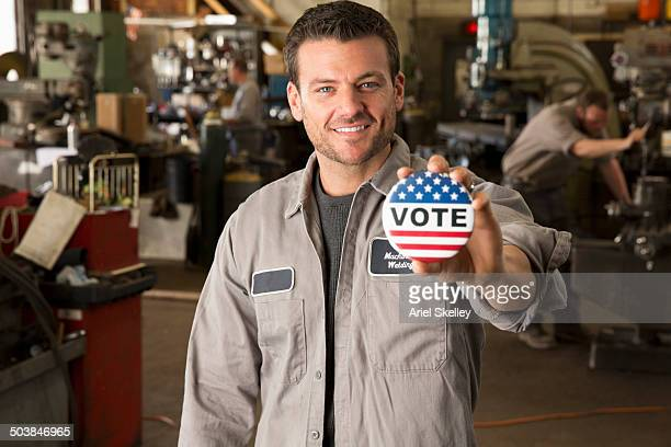 Machinist holding Vote' button in garage