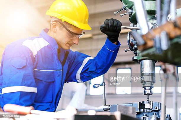 Machinist working on drill press in factory