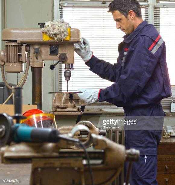 Machinist working on drill press in workshop