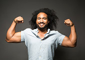 Muscular diverse Australian / Pacific Islander flexing biceps, strength, body building,