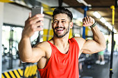 Muscular man making a selfie in a gym, bragging and showing muscles. About 20 years old Caucasian man.