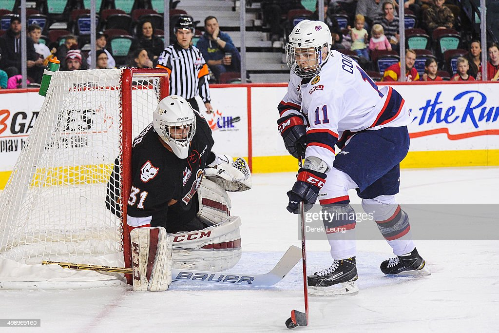 Mack Shields #31 of the Calgary Hitmen defends net against Taylor Cooper #11 of the Regina Pats during a WHL game at Scotiabank Saddledome on November 27, 2015 in Calgary, Alberta, Canada.