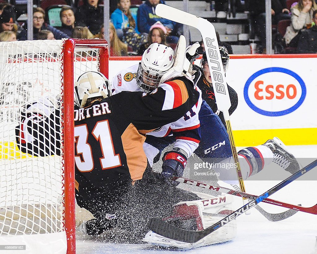 Mack Shields #31 of the Calgary Hitmen gets knocked down by Taylor Cooper #11 of the Regina Pats during a WHL game at Scotiabank Saddledome on November 27, 2015 in Calgary, Alberta, Canada.