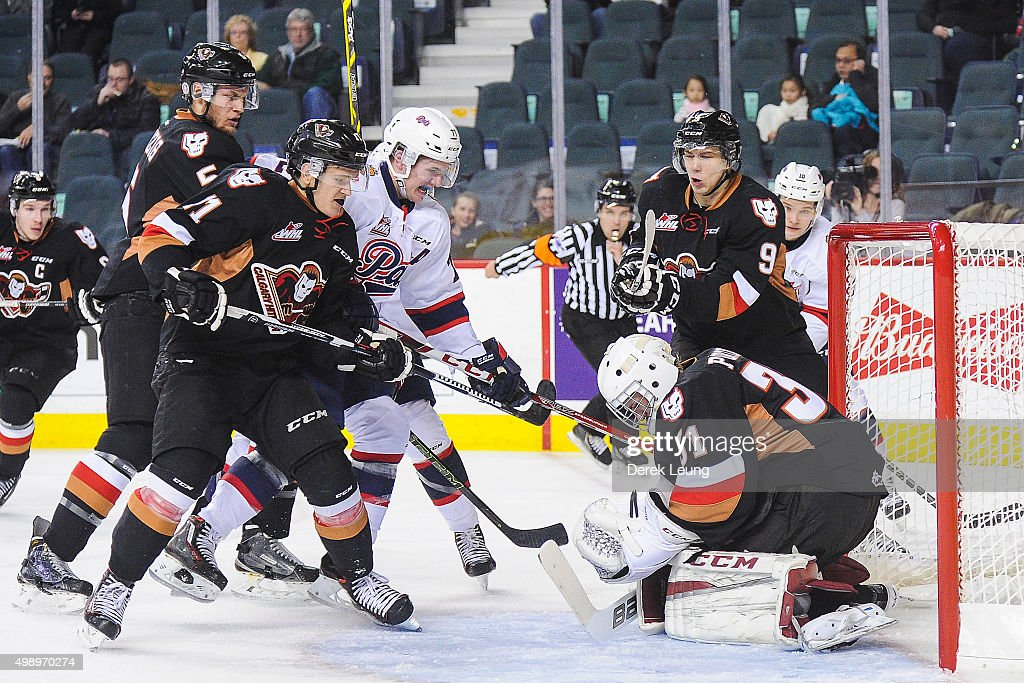 Mack Shields #31 of the Calgary Hitmen stops the shot of Adam Brooks #77 of the Regina Pats during a WHL game at Scotiabank Saddledome on November 27, 2015 in Calgary, Alberta, Canada.