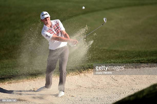 Mackenzie Hughes of Canada hits his third shot from a greenside bunker on the 18th hole during the first round of the Shell Houston Open at the Golf...