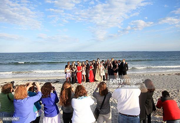 Mackenzie Leighton a junior at Cape Elizabeth High School and her date Connor Maguire a senior join their friends as parents photograph them on the...