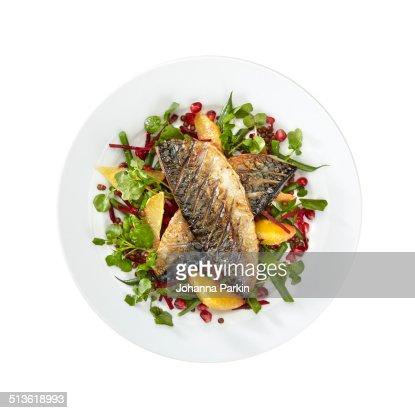 Mackerel and orange salad on white plate