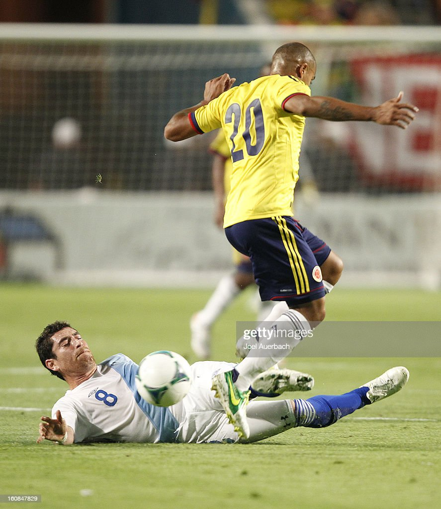 Macnelly Torres #20 of Colombia trips over Jean Marquez #8 of Guatemala as he goes for the ball on February 6, 2013 at SunLife Stadium Stadium in Miami Gardens, Florida.