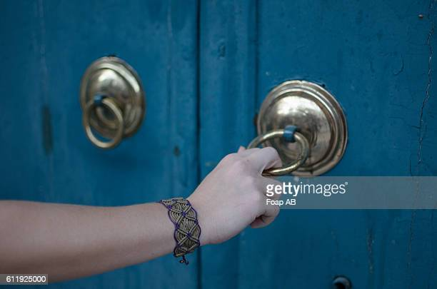 Macrame bracelet in hand holding knob door