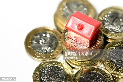 Macro close up of a Miniature house resting on new pound coins : Stock Photo