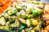 Macro closeup of roasted green brussels sprouts cabbage in tray on display in buffet, catering, deli, store, shop grocery market fresh, cheese