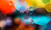 Close up macro image depicting droplets of oil in water on a multi colored background. The oil forms interesting circles and spheres in the water, and colorful background produces and abstract effect.