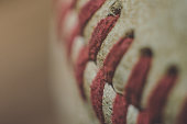 A close up shot of the details of a baseball.