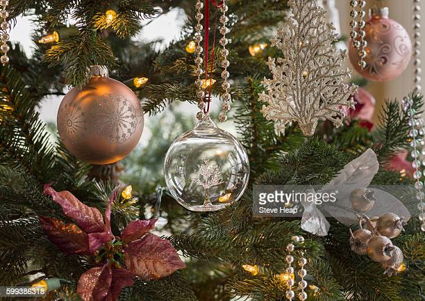 Macro shot of glass globe with tree on indoor christmas tree with decorations