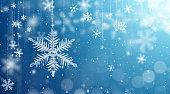 Macro snowflake and fallen defocused snowflakes on blue background