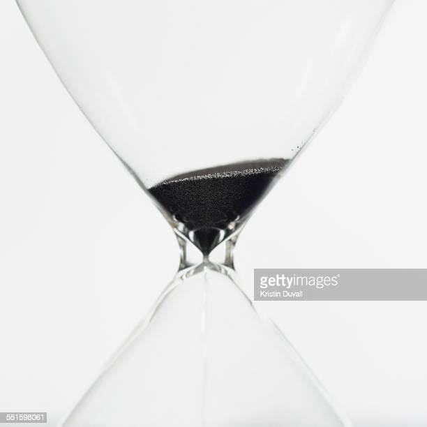Macro view of sand in hourglass on white