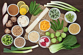 Macrobiotic diet food with japanese udon noodles, tofu, miso and wasabi paste, grains, legumes, vegetables and wasbai nuts with foods high in protein, antioxidants, fibre, vitamins and minerals. On ba