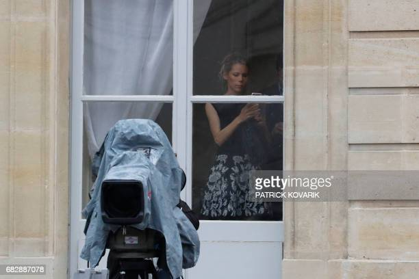 Macron's stepdaughter Tiphaine Auziere looks on from a window of the Elysee presidential Palace for the handover and inauguration ceremonies on May...