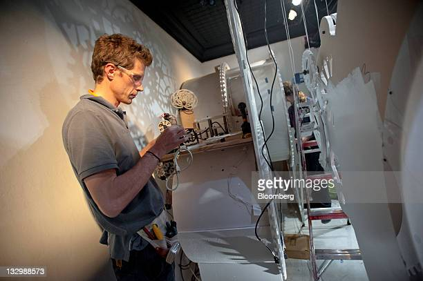 A Macy's Inc window installer works to create the holiday display in New York US on Tuesday Nov 16 2011 Retail sales rose more than projected in...