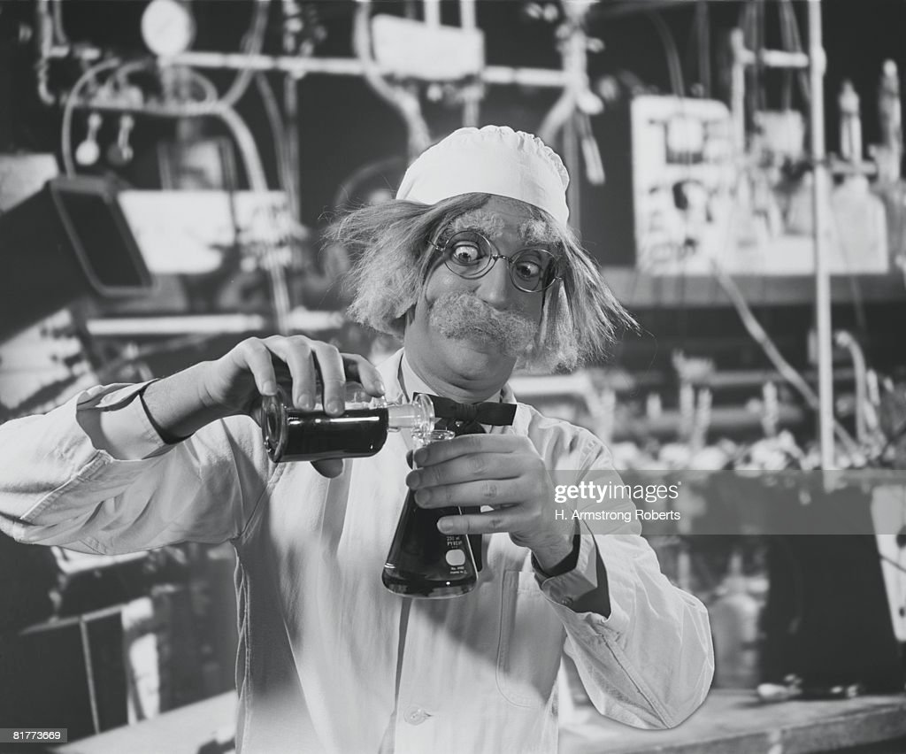 Mad scientist in laboratory, mixing chemicals. : Stock Photo