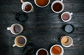 Circle of twelve various tea cups and mugs. Flat lay