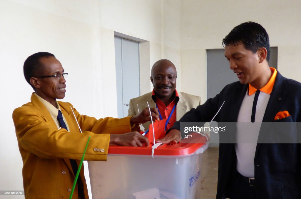 Madagascar's President <a gi-track='captionPersonalityLinkClicked' href=/galleries/search?phrase=Andry+Rajoelina&family=editorial&specificpeople=4758126 ng-click='$event.stopPropagation()'>Andry Rajoelina</a> (R) casts his ballot in a polling station during the presidential election on December 20, 2013 in Antananarivo, Madagascar. Madagascans return to polling stations on Friday to choose a new president in a run-off vote aimed at ending a political and economic crisis sparked by a coup four years ago.