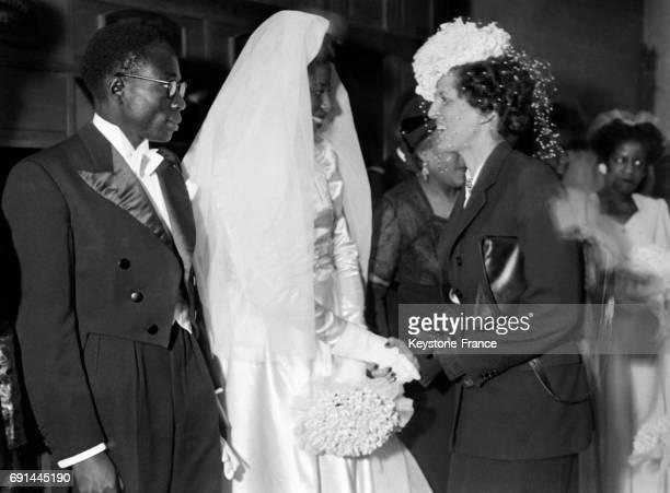 Madame Georges Bidault félicite les jeunes époux le député sénégalais Léopold Sédar Senghor et Ginette Eboué fille du premier gouverneur général noir...