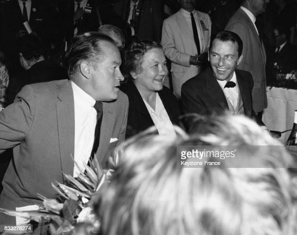 Madame Khrouchtchev souriante entourée à sa gauche de Bob Hope et à sa droite de Franck Sinatra lors d'un déjeuner dans les studio de la Fox à...