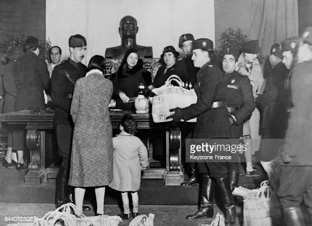 Madame Mussolini au centre sous le buste de son époux préside la distribution de vivres à la Villa Torlonia à Rome Italie le 24 décembre 1935
