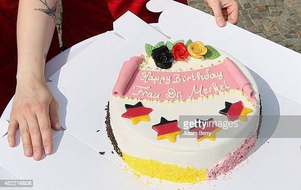 Madame Tussauds employee unpacks a birthday cake next to a figure of German Chancellor Angela Merkel in front of the Brandenburg Gate on July 16 2014...