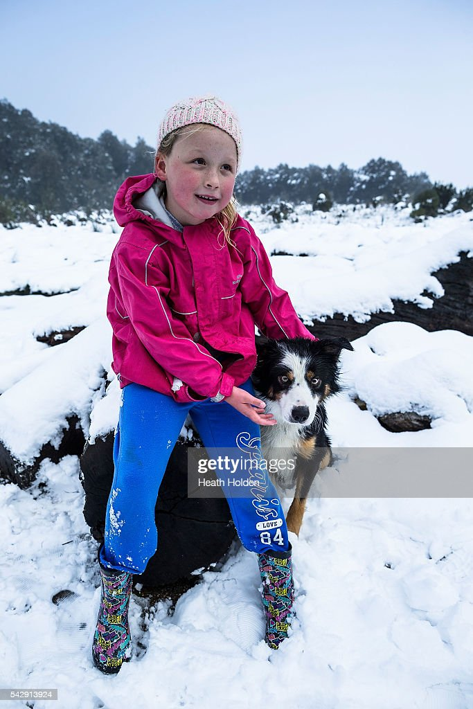 Maddie Behrens (6yrs) enjoys the winter snowfall with Cooper the collie on June 25, 2016 in Cradle Mountain, Australia. Snow has been forecast across Eastern Australia as cold front continues to bring low temperatures, rain and potentially damaging winds.