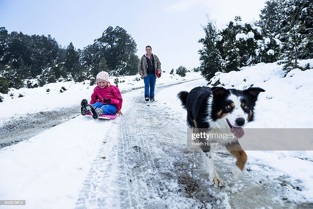 Maddie Behrens (6yrs) enjoys the winter snowfall with her mum, Erika Behrens and Cooper the collie on June 25, 2016 in Cradle Mountain, Australia. Snow has been forecast across Eastern Australia as cold front continues to bring low temperatures, rain and potentially damaging winds.