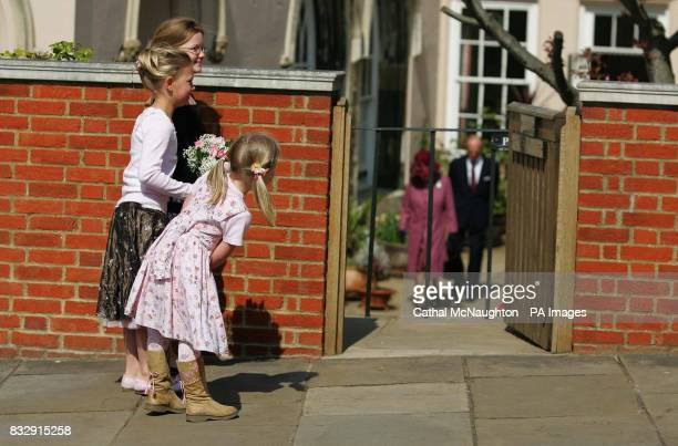 Maddie Gainer with her sisters Natasha and Abigail peers around the wall to catch a glimpse of HRH Queen Elizabeth II and the Duke of Edinburgh as...