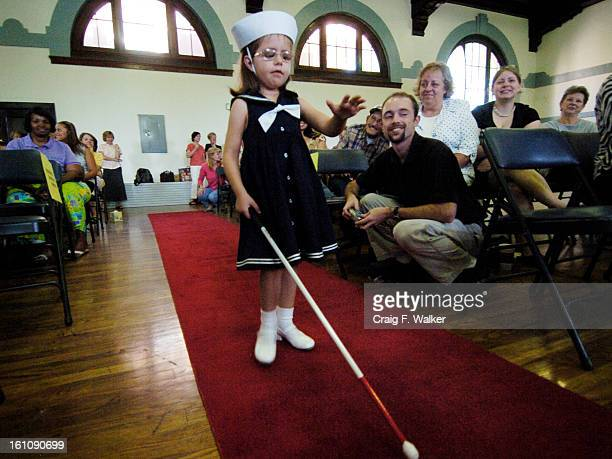 JUNE 15 2006 DENVER CO Maddie Stallman uses her cane as she makes her way down the red carpet during a graduation celebration for preschoolers at the...